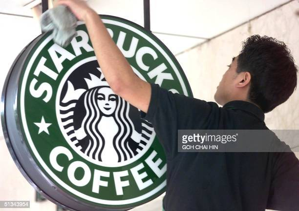 Worker cleans the sign outside a global coffee franchise Starbucks outlet in Beijing 25 October 2000. Coffee was introduced to China in the 1920s,...