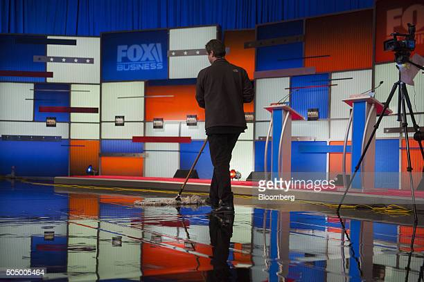 A worker cleans the stage floor ahead of the Republican presidential candidate debate at the North Charleston Coliseum and Performing Arts Center in...