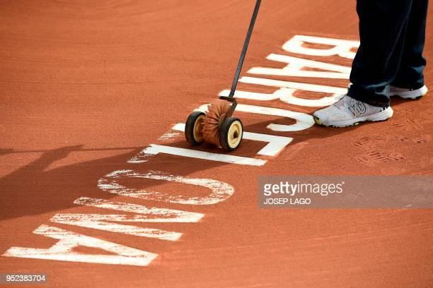 TOPSHOT A worker cleans the tennis court ground during the Barcelona Open ATP tennis tournament semifinals in Barcelona on April 28 2018