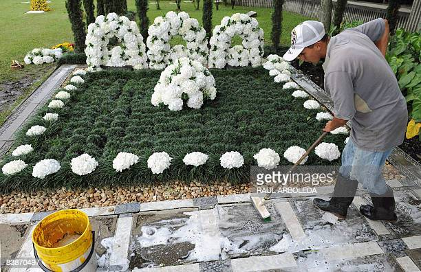 A worker cleans the tombstone of Colombian drug lord Pablo Escobar on December 1 in Medellin Antioquia department Colombia on the anniversary of his...