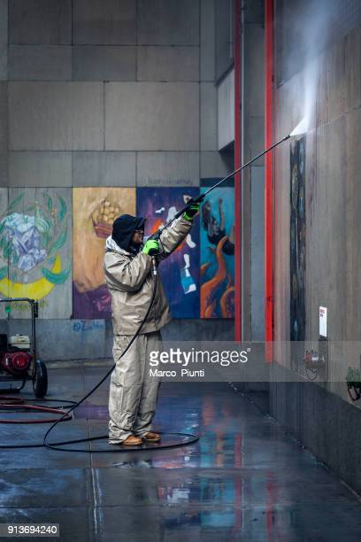 Worker cleans the wall from graffiti