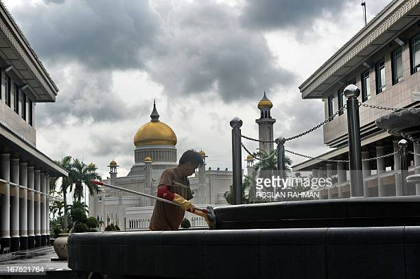 A worker cleans the water fountain against the backdrop of Sultan Omar Ali Saifuddin mosque in the capital city Bandar Seri Begawan on April 26 2013...