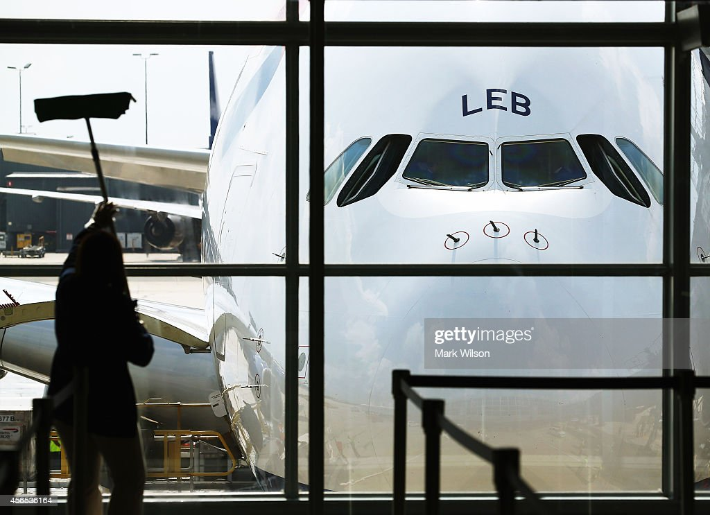 A worker cleans the windows in front of British Airways' new super jumbo Airbus A380 after it arrived at Washington Dulles International Airport October 2, 2014 in Dulles, Virginia. British Airways introduced the first Airbus A380 nonstop service between London Heathrow and Washington Dulles International Airport.