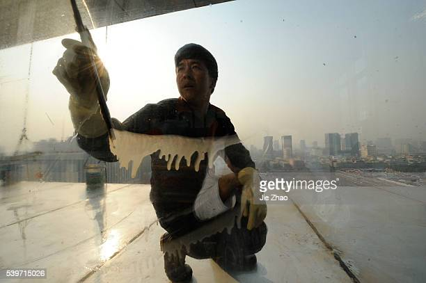 A worker cleans the windows of a newly built office building in Taiyuan Shanxi province October 31 2010