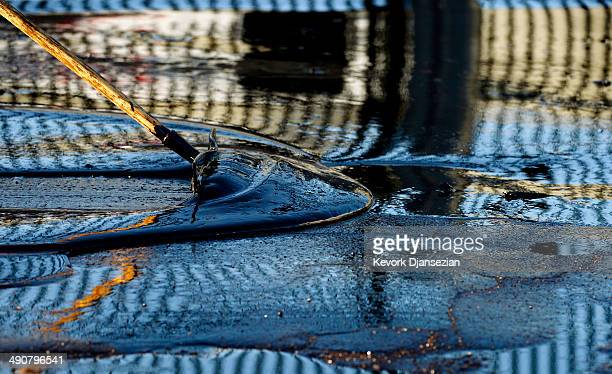 A worker cleans up an oil from a pipe that burst causing about 10000 gallon of crude oil spill onto streets covering an area of about a halfmile May...