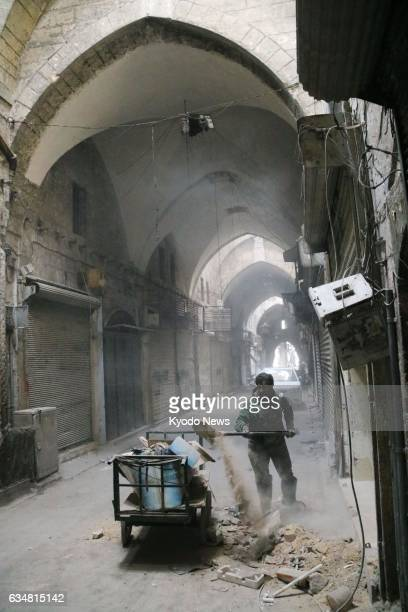 A worker cleans up debris at a souk in the old city of Aleppo northern Syria on Feb 8 about two month after Syrian government troops seized control...