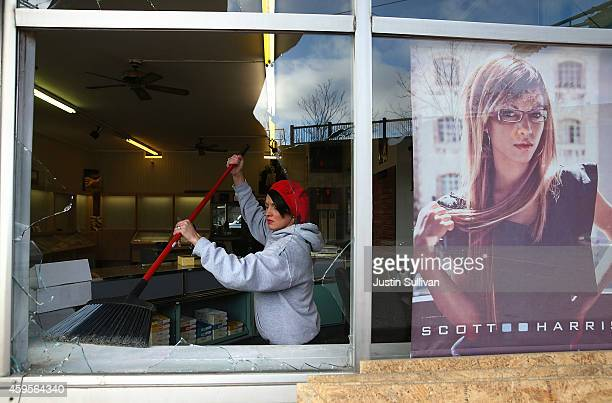 A worker cleans up glass at a business that was damaged during a demonstration on November 25 2014 in Ferguson Missouri Demonstrators caused...