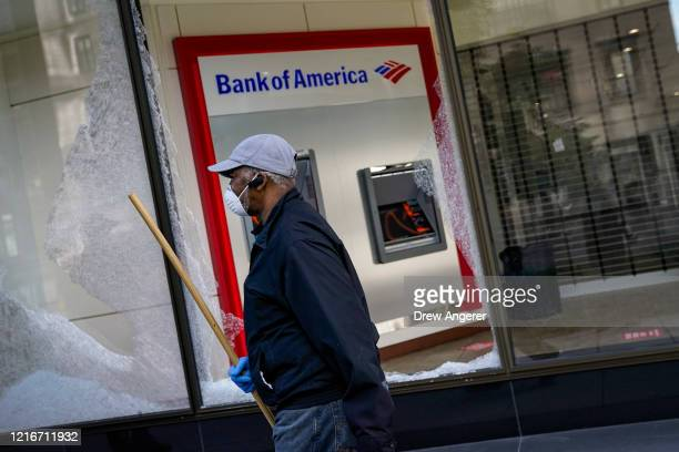 A worker cleans up near a Bank of America that was damaged during overnight unrest June 1 2020 in Washington DC Protests and riots continue across...
