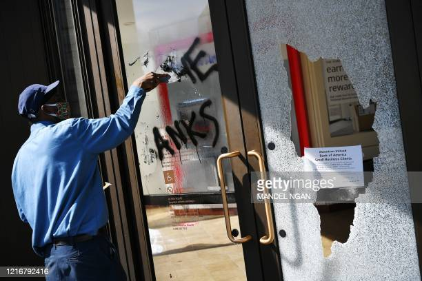 A worker cleans up the front of a damaged bank in the aftermath of rioting near the White House in Washington DC on June 1 2020 Police fired tear gas...