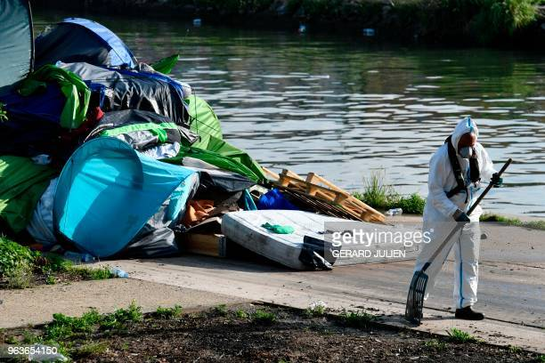 A worker cleans up the Millenaire migrants makeshift camp along the Canal de SaintDenis near Porte de la Villette northern Paris following its...