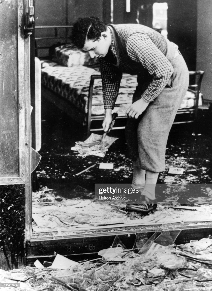 A worker clearing broken glass of a Jewish shop following the anti-Jewish riots of Kristallnacht in Berlin.