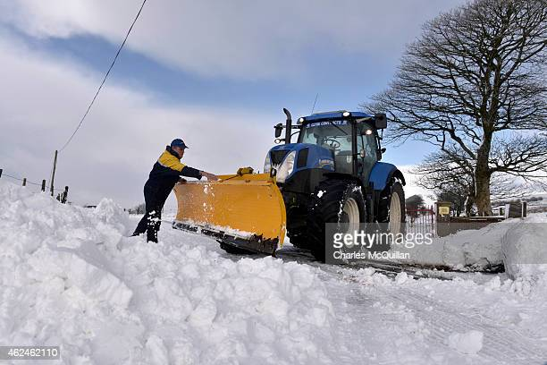 A worker clearing the roads with his plow clears snow from his blade on January 29 2015 in Belfast United Kingdom Continued snow fall and freezing...