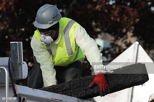 A worker clears charred debris following a warehouse fire that has claimed the lives of at least thirtythree people on December 4 2016 in Oakland...