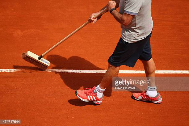A worker clears clay dust from the court lines on day two of the 2015 French Open at Roland Garros on May 25 2015 in Paris France