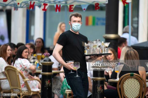 Worker clears empty glasses from the Gin and Juice bar gin bar on August 08, 2020 in Cardiff, Wales. Coronavirus lockdown measures continue to be...