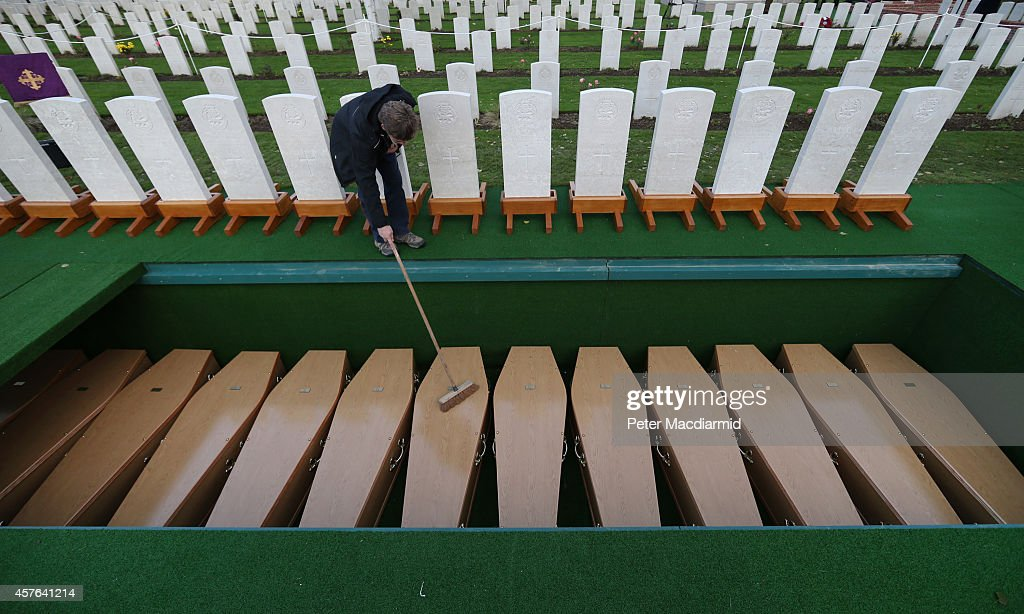 A worker clears leaves from coffins containing the remains of 15 British World War One soldiers at the Commonwealth War Graves Commission Y-Farm Cemetery on October 22, 2014 in Bois-Grenier, France. The remains of 15 Soldiers of the 2nd Battalion York and Lancaster Regiment of the British army, who were killed in the opening months of World War One on October 18, 1914 were discovered in 2009 during construction work near the French village of Beaucamps-Ligny. Using DNA tests on samples provided by their surviving relatives it has been possible to identify 11 of the soldiers. Those who have been positively identified and whose surviving family members have been traced are: Private Herbert Ernest Allcock, Private John Brameld, Private William Butterworth, Corporal Francis Carr Dyson, Private Walter Ellis, Private John Willie Jarvis, Private Leonard Arthur Morley, Private Ernest Oxer, Private John Richmond, Private William Alfred Singyard and Lance Corporal William Henry Warr. Members of their families will attend the service.