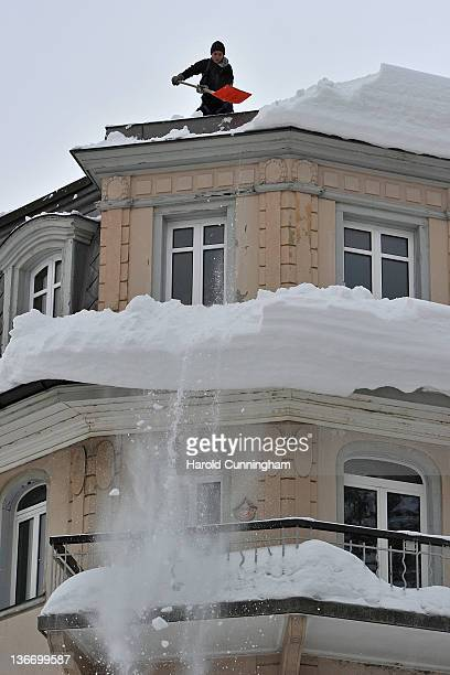 A worker clears snow on a roof on January 10 2012 in Davos Switzerland The World Economic Forum which gathers the World's top leaders runs from...