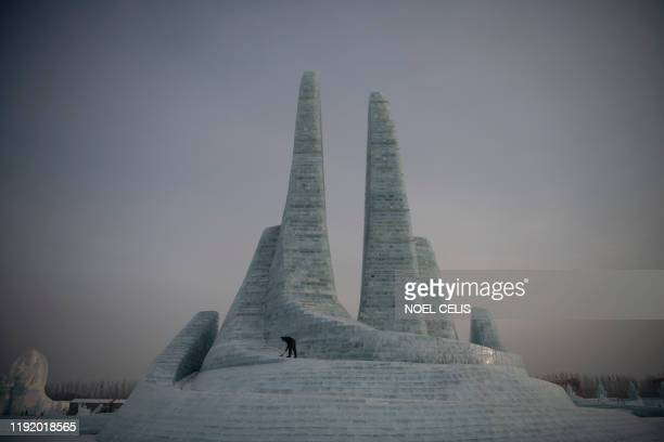 TOPSHOT A worker clears some snow before tourists arrive at the Harbin International Ice and Snow Festival in Harbin in China's northeast...