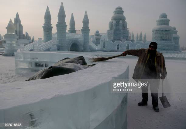 A worker clears some snow before tourists arrive at the Harbin International Ice and Snow Festival in Harbin in China's northeast Heilongjiang...