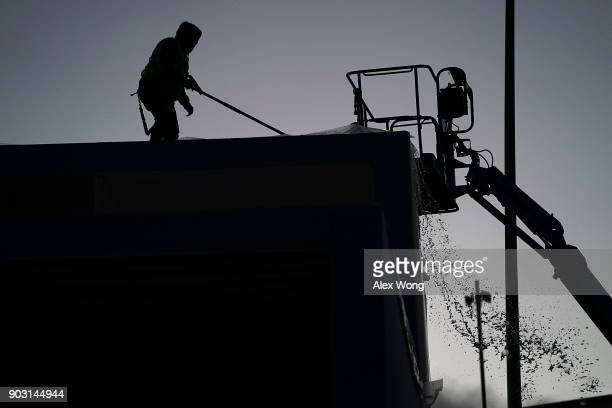 A worker clears up water collected on a tarp atop of the roof of the Google booth which was closed on the first day of CES 2018 at the Las Vegas...