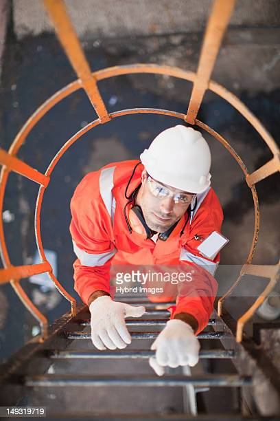worker climbing ladder at oil refinery - gas refinery stock photos and pictures