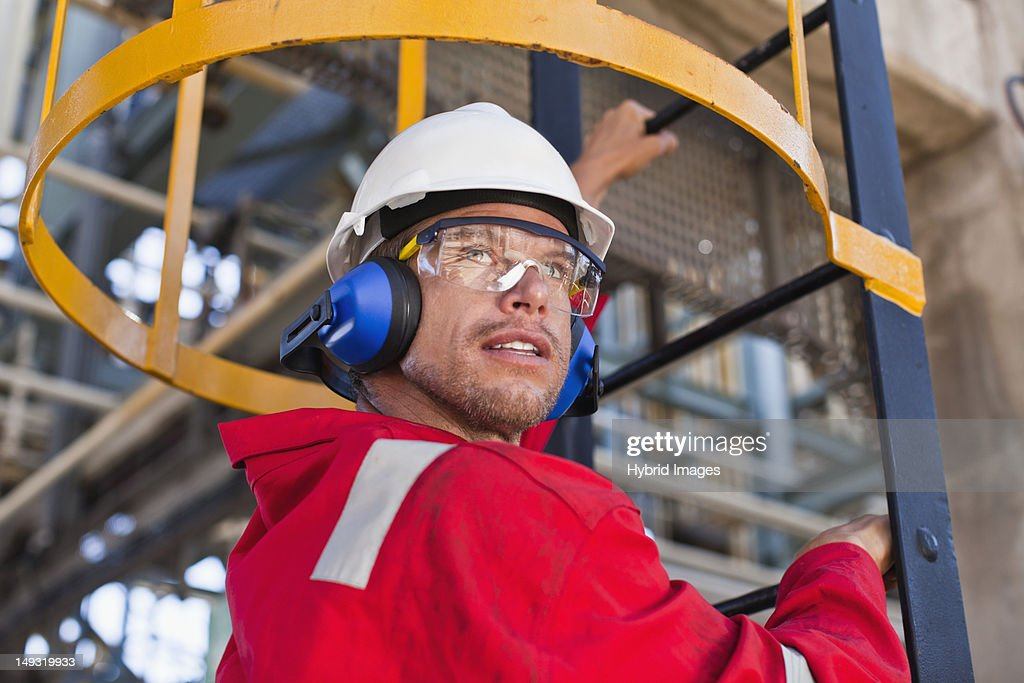 Worker climbing ladder at oil refinery : Stock Photo