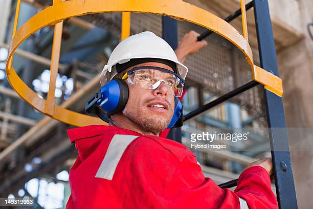 worker climbing ladder at oil refinery - sports helmet stock pictures, royalty-free photos & images