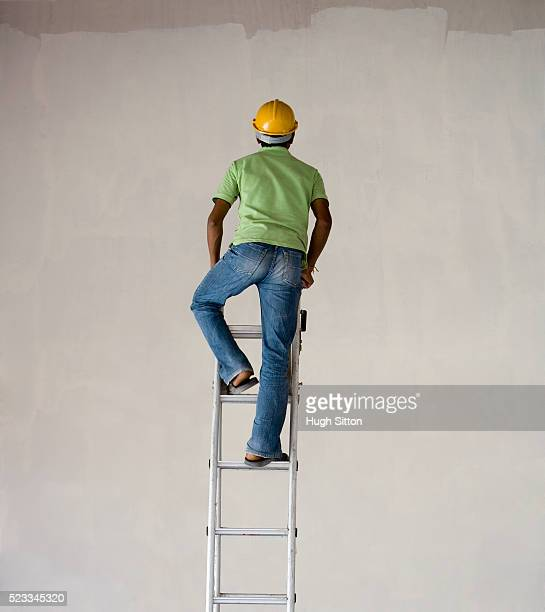 Worker Climbing Ladder