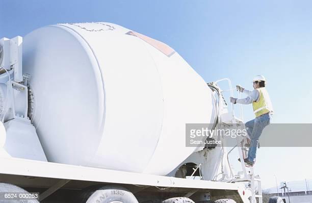 Worker Climbing on Dump Truck