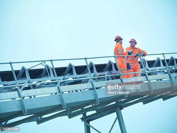 Worker climbing screening conveyor