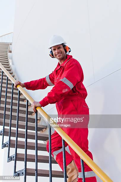 Worker climbing steps at chemical plant