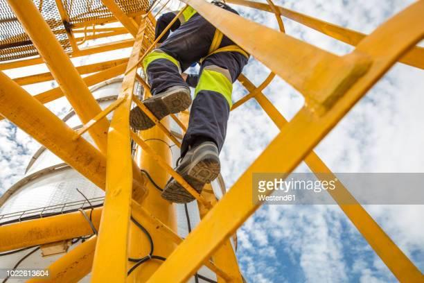 worker climbing up ladder at tank - saúde e segurança ocupacional - fotografias e filmes do acervo
