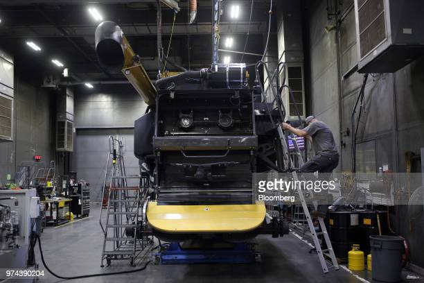 A worker climbs a ladder while assembling a combine harvester at the CLAAS of America Inc production facility in Omaha Nebraska US on Wednesday June...