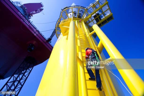 a worker climbs a wind turbine nex to a jack up barge conastructing the offshore wind farm. - sicherheitsausrüstung stock-fotos und bilder