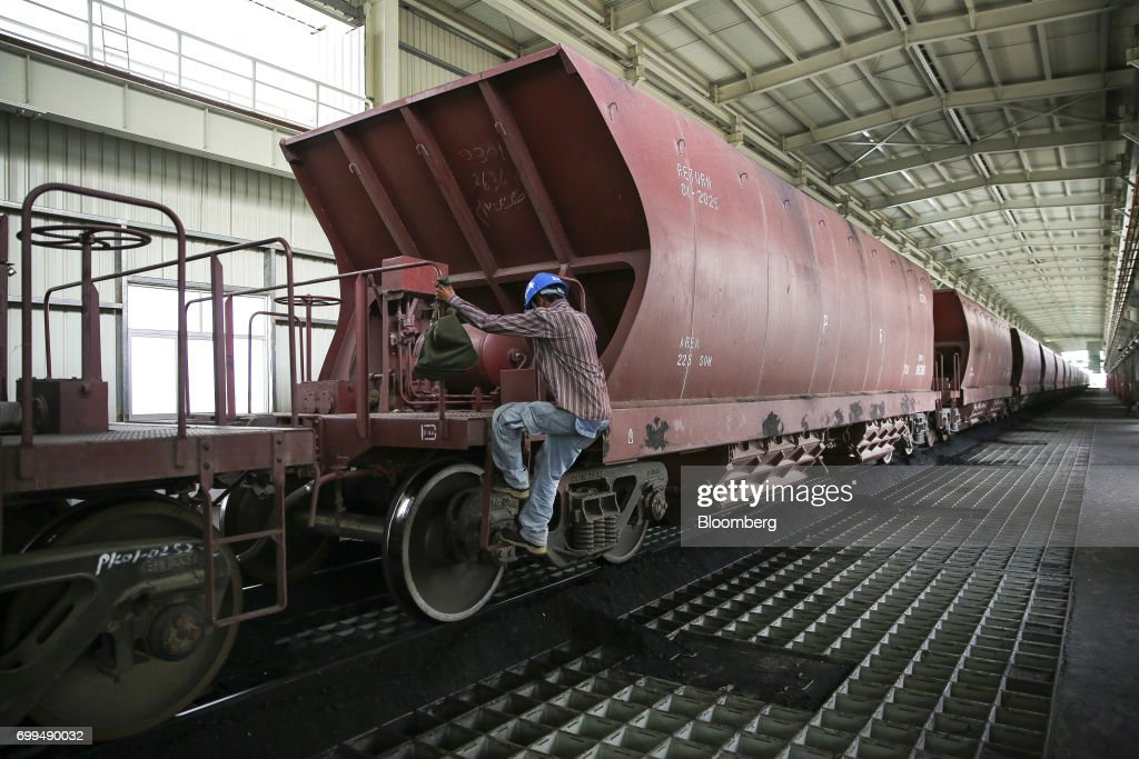 A worker climbs onto a rail freight wagon used for delivering coal at the Sahiwal coal power plant owned by China`s stateowned Huaneng Shandong Rui...