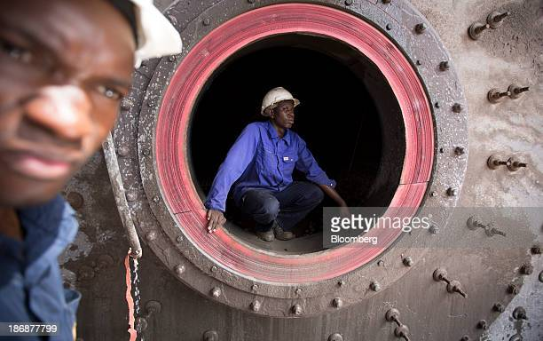 A worker climbs out of a mill grinder used for iron ore in the production plant at the gold mine operated by Randgold Resources Ltd in Loulo Mali on...