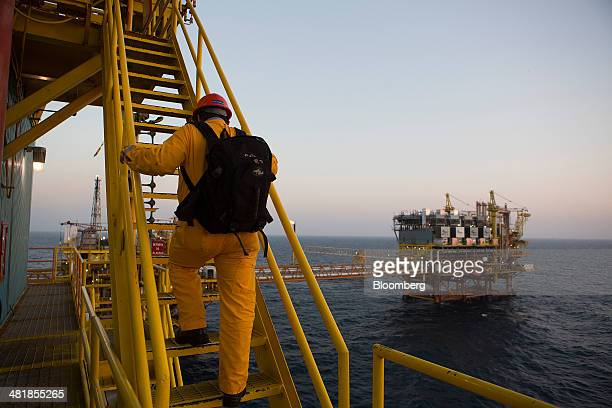 A worker climbs stairs to get to the heliport at the Petroleos Mexicanos PolA Platform complex located on the continental shelf in the Gulf of Mexico...