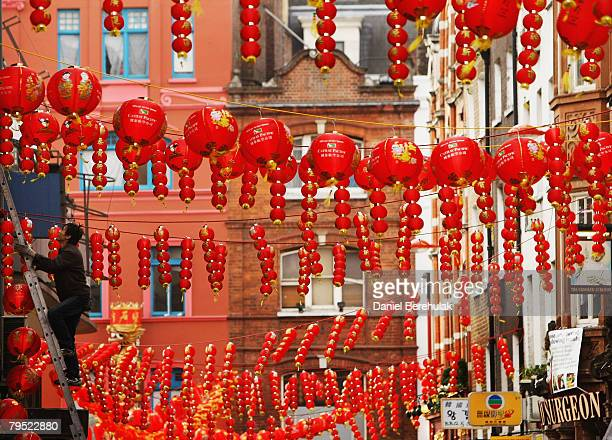 A worker climbs up a ladder to put up lanterns in China Town a day before Chinese new years eve on February 5 2008 in London England In Chinese...