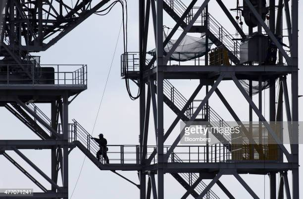 A worker climbs up a supporting tower of a conveyor carrying excavated soil to a residential area under construction in Rikuzentakata Iwate...