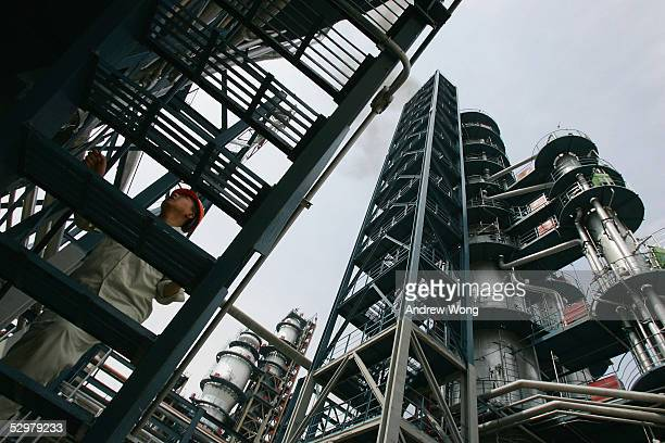 A worker climbs up an oil facility staircase at the Yanlian Oil Refinery on May 25 2005 in Luochuan county of Shaanxi Province in China About 50...