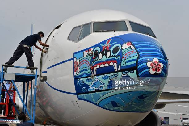 Worker closes a door of a Garuda Indonesia Boeing 373-800 NG with a new face mask design as part of a campaign to promote the wearing of face masks...