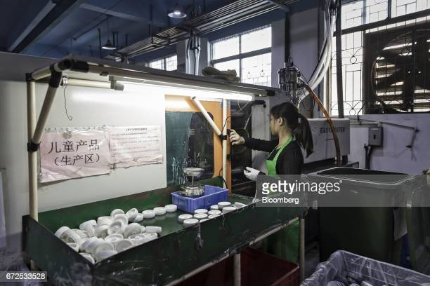 A worker closes a sliding door at a workstation that will be replaced by an industrial robot at a factory operated by the Guangdong Shiyi Furniture...