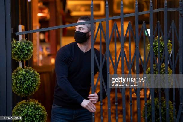 Worker closes the front gate to a bar on St. Mary Street on October 23, 2020 in Cardiff, Wales. Wales will go into a national lockdown from Friday...