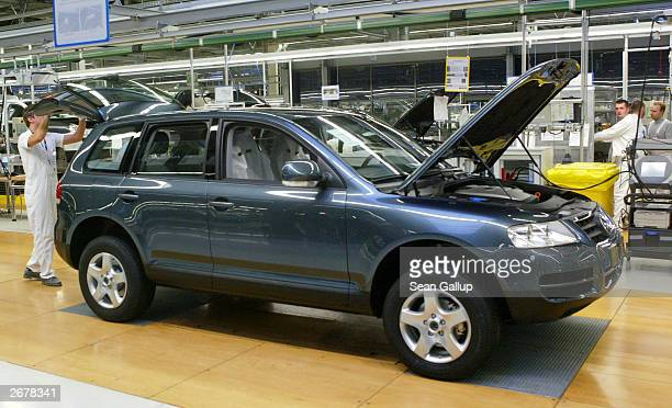 Worker closes the rear door of a Volkswagen Touareg sport utility vehicle October 29, 2003 at the Volkswagen factory just outside Bratislava,...