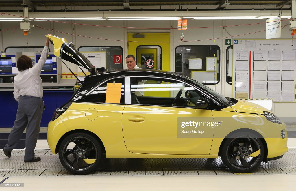 A worker closes the trunk of a finished Opel Adam car at the assembly line shortly after a celebration to mark the launch of the new Opel compact car at the Opel factory on January 10, 2013 in Eisenach, Germany. Opel employees hope the car will help the compny return to profits after years of sagging sales and the announcement of the Bochum factory closure in 2016.