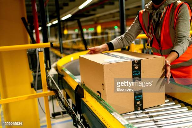Worker collects an Amazon Prime customer order package from a conveyor at an Amazon.com Inc. Fulfillment center in Frankenthal, Germany, on Tuesday,...