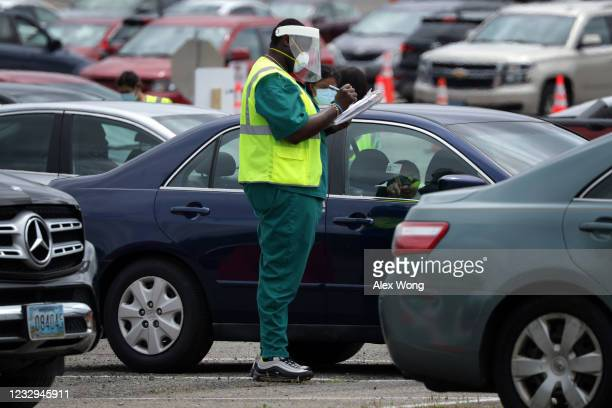 Worker collects information from local residents as he check them in at a drive-thru coronavirus testing location at Six Flags America May 29, 2020...