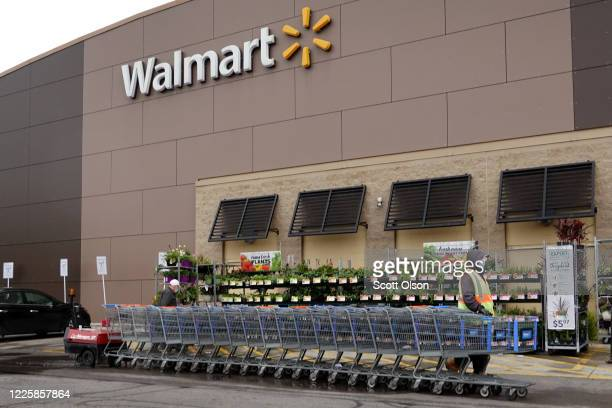 Worker collects shopping carts at a Walmart store on May 19, 2020 in Chicago, Illinois. Walmart reported a 74% increase in U.S. Online sales for the...