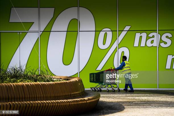 A worker collects shopping carts outside an advertisement for 70 percent discounts at the Dolce Vita Tejo shopping mall operated by AXA Real Estate...