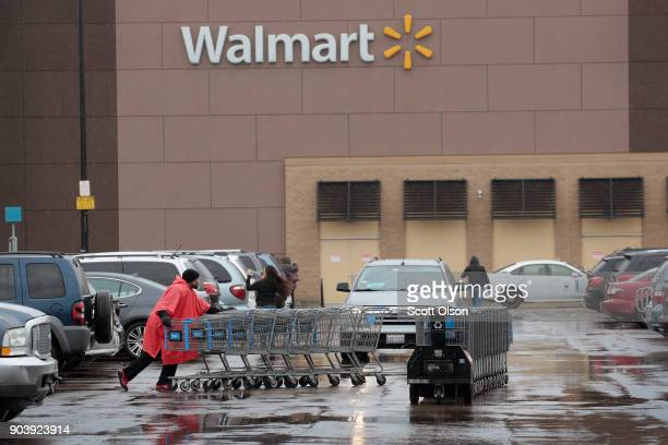 A worker collects shopping carts outside Walmart store on January 11 2018 in Chicago Illinois Walmart announced today it would use savings from the...
